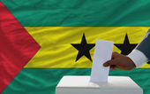 Man voting on elections in front of national flag of sao tome pr — Stock Photo
