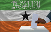 Man voting on elections in front of national flag of somaliland — Stock Photo