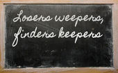 Expression - Losers weepers, finders keepers - written on a sch — Stock Photo
