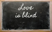 Expression - Love is blind - written on a school blackboard wit — Стоковое фото