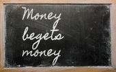 Uttryck - pengar föder pengar - skrivit på en skola blackboar — Stockfoto