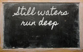 Expression - Still waters run deep - written on a school blackb — Foto de Stock