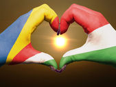Heart and love gesture by hands colored in seychelles flag durin — Stock Photo