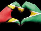 Gesto de corazón y amor por las manos de colores en la bandera de guyana para touri — Foto de Stock