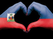 Heart and love gesture by hands colored in haiti flag for touris — Stok fotoğraf