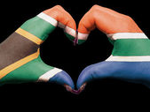 Heart and love gesture by hands colored in south africa flag for — Stock Photo