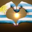 Heart and love gesture by hands colored in uruguay flag during b — Stock Photo