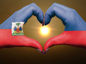 Heart and love gesture by hands colored in haiti flag during bea — Stock Photo