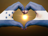 Heart and love gesture by hands colored in honduras flag during — Stock Photo