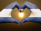 Heart and love gesture by hands colored in nicaragua flag during — Stock Photo