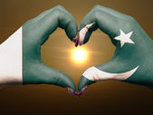 Heart and love gesture by hands colored in pakistan flag during — Stock Photo