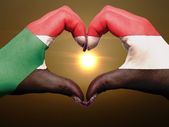 Heart and love gesture by hands colored in sudan flag during bea — Stock Photo