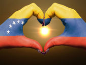 Heart and love gesture by hands colored in venezuela flag during — Stock Photo