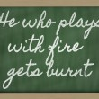 Expression -  He who plays with fire gets burnt - written on a s - Stock Photo
