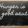 Stock Photo: Expression - Hunger is good sauce - written on school blackb