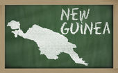 Outline map of new guinea on blackboard — Stock Photo