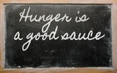 Expression - Hunger is a good sauce - written on a school blackb — Stok fotoğraf