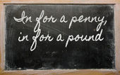 Expression - In for a penny, in for a pound - written on a scho — Stok fotoğraf