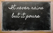 Expression - It never rains but it pours - written on a school — Foto Stock