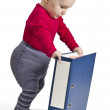 Small child standing next to blue ring binder - Stock Photo