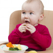 Royalty-Free Stock Photo: Young child eating in high chair
