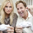 Married Couple Having Fun Playing Video Console Game - 