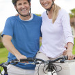 Stock Photo: Happy Man & Woman Couple Riding Bikes
