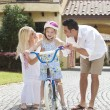 Stock Photo: Family WIth Girl Riding Bike & Happy Parents