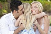Mädchen umarmen glückliche eltern im park oder im garten — Stockfoto