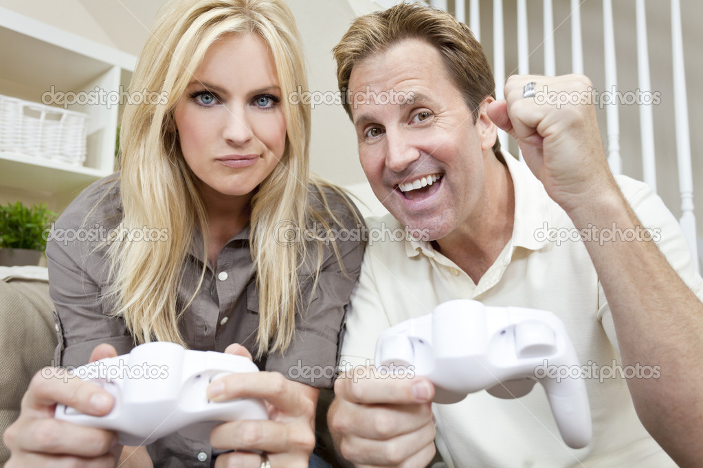 Young married couple, man and woman, having fun playing video console games together. The man has just beaten the woman, he is celebrating, she is unhappy. — Stock Photo #8438087