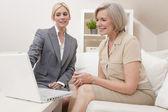 一个高级的女人提供咨询意见的膝上型计算机的售货员 — 图库照片