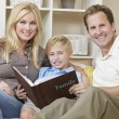 Happy Family Sitting on Sofa Looking at Photo Album — Stock Photo