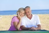 Happy Senior Couple Using Cell Phone at Table By Beach — Stock Photo