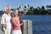 Lyckliga äldre par vajande utanför i solen vid havet — Stockfoto