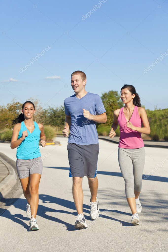 Three fit and healthy interracial young adult friends running or jogging together  Stock Photo #8462490