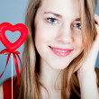 Beautiful girl blonde with red heart in hand — Stock Photo