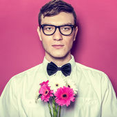 Young beautiful man with flowers — Stock Photo