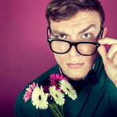Portrait of a man in big glasses with flowers — Stock Photo