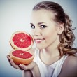 Portrait of young attractive woman with grapefruit - Stock Photo