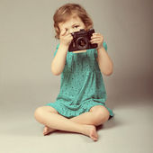 Portrait of baby girl holding photo camera — Stock Photo