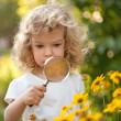 Stock Photo: Child explorer flowers in garden