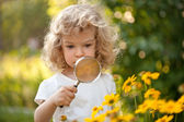 Child explorer flowers in garden — Stock Photo