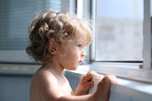 Child looking into window — Stock Photo