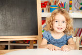 Smiling schoolchild in a class — Stock Photo