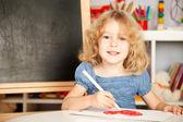 Happy child painting heart — Stock Photo