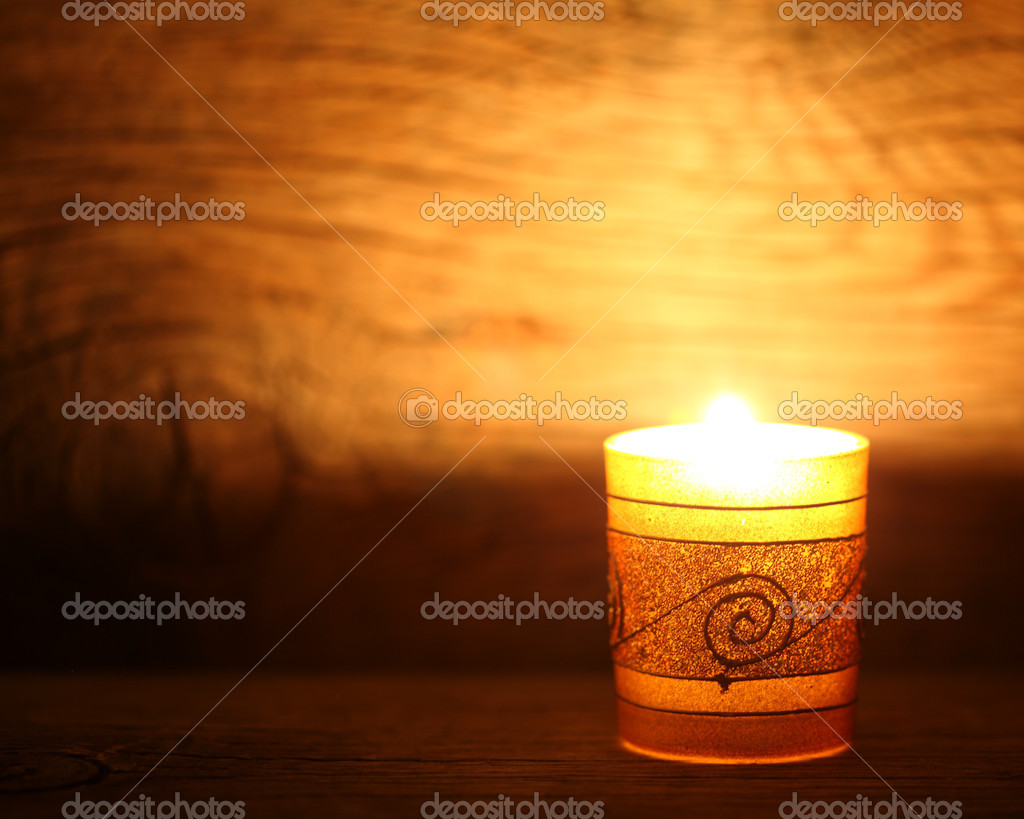 Burning gold candle on old wood  Stock Photo #8140470