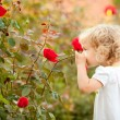 Beautiful child smelling rose — Stock Photo #8485587