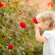 Stock Photo: Beautiful child smelling rose