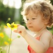 Child touching spring flower — Stock Photo #8485657