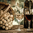 Wine bottles, two glasses and grapes in basket — Stock Photo #8485744